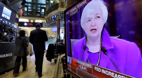 Federal Reserve Chair Janet Yellen's Washington news conference is shown on a television screen on the floor of the New York Stock Exchange, Wednesday, Dec. 16, 2015. The Fed's move to lift its key rate by a quarter-point to a range of 0.25 percent to 0.5 percent ends an extraordinary seven-year period of near-zero rates that began at the depths of the 2008 financial crisis. (Richard Drew/AP)