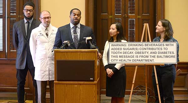 A proposed bill  would require warning signs in Baltimore stores that sell sugary beverages.  Seen here with a sample sign are, from left, Aaron Maybin of Baltimore, a former NFL player with the Jets, Bills, Bengals; Dr. Richard Bruno, Johns Hopkins Bloomberg School of Public Health; Councilman Nick Mosby; Dr. Leana Wen, Commissioner of Heath Baltimore City; Rovi Rawl, Executive Director of Sugar Free Kids Maryland. (The Daily Record/Maximilian Franz)