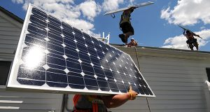 Workers install a solar panel. (File)