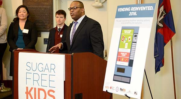 "Akil Patterson, Deputy Director of Sugar Free Kids Maryland, at the announcement that they will be proposing the ""Maryland Health Vending Act"" during the 2016 Legislative session, which would require vending machines to offer more healthy food options on state property.  (The Daily Record / Maximilian Franz)"