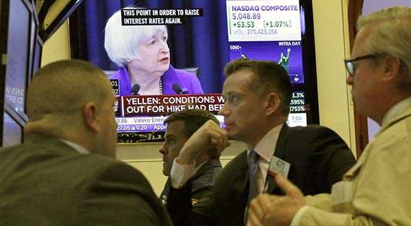 In this Dec. 16, 2015, file photo, Federal Reserve Chair Janet Yellen's Washington news conference is shown on a television screen on the floor of the New York Stock Exchange.  (AP Photo/Richard Drew, File)
