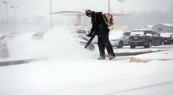 George Morris, with Standard Parking, works on clearing an entrance to airport parking as snow falls Friday morning, Jan. 22, 2016, in Roanoke, Va. Airlines have canceled more than 2,700 flights Friday to, from or within the U.S., as a blizzard swings up the East Coast, according to flight tracking service FlightAware. (Stephanie Klein-Davis/The Roanoke Times via AP)
