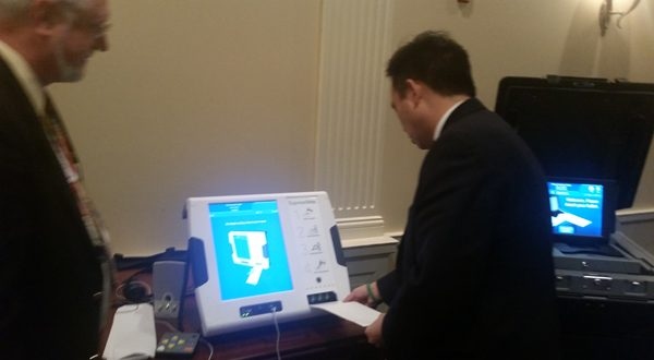 Delegate Mark Chang, D-Anne Arundel, puts a test paper ballot into a touch-screen kiosk Friday in Annapolis. The paper voting system is expected to be in place for the April primary election. (Rachel Bluth / Capital News Service)