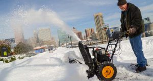 Jesse Hall, assistant director of facilities at the Maryland Science Center, blows snow at the Inner Harbor. (The Daily Record / Maximilian Franz)