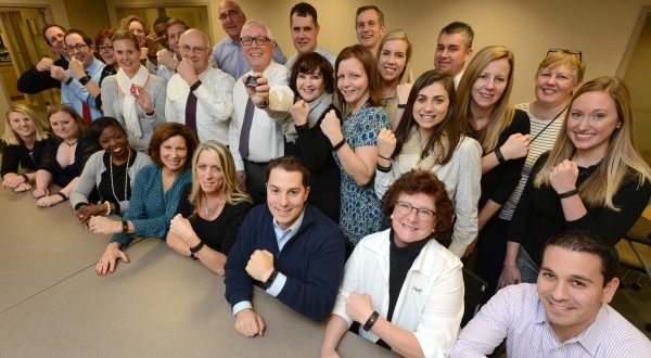 Employees at Rosenberg Martin Greenberg LLP in Baltimore show off their wearable fitness devices that are being used to track steps for an office-wide wellness challenge. 'It's not only getting us out there to exercise and be more conscious about moving around, but there's also an encouraging team aspect,' one employee says of the competition. (Maximilian Franz/The Daily Record)