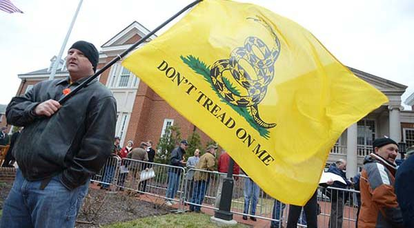 A pro-gun activist holds a Don't Tread on Me flag outside of the Lowe House office Building in Annapolis before a 2-13 hearing on gun legislation. (File)
