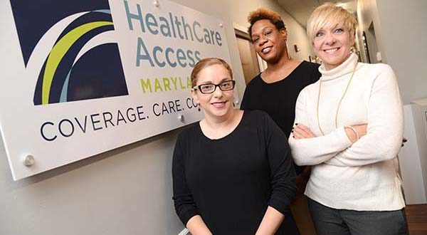 From Left: Traci Kodeck, Interim CEO; Tashima Ricks, RN, Clinical Director of Population Health; Susan Markley, Vice President, Business Development, pictured in front of the Healthcare Access Maryland sign in their office lobby. (The Daily Record/Maximilian Franz).