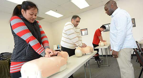 From Left, students Tara Gurung, Chetan Sharma, and Hyeonho Jeong, being taught CPR by, Colin Stewart, CPR Instructor, in a Healthcare Provider CPR class at The World Institute of Safety. (The Daily Record/Maximilian Franz).