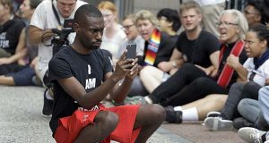 In an Aug. 10, 2015 file photo, protester and social media activist DeRay McKesson records outside the Thomas F. Eagleton Federal Courthouse in St. Louis. (AP Photo/Jeff Roberson, File)
