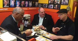 Gov. Larry Hogan and Lt. Gov. Boyd Rutherford sit in the reserved Governor's Table with Teddy Levitt, owner of Chick and Ruth's Delly. (The Daily Record / Bryan P. Sears)