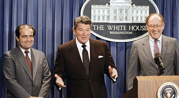 In this June 17, 1986 file photo, President Ronald Reagan speaks at a news briefing at the White House in Washington, where he announced the nomination of Antonin Scalia, left, to the Supreme Court as a result of Chief Justice Warren E. Burger's resignation. William Rehnquist is at right. On Saturday, Feb. 13, 2016, the U.S. Marshals Service confirmed that Justice Scalia has died at the age of 79. (AP Photo/Ron Edmonds)