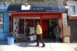 William Hayward, 66, walks by Sharp Dressed Man, a non- profit that helps connect donated dress clothes with men that need them. The property they occupy at 235 Park Avenue suffered an electrical fire yesterday evening that condemned the building and will need extensive repair work or they will need a new storefront before they reopen. (The Daily Record/Maximilian Franz).