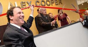 Baltimore County Executive Kevin Kamenetz helps hold the ribbon for Joseph Cooper while he officially cuts it to open the new space. (The Daily Record / Maximilian Franz)