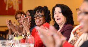 Attendees at the Dining Divas' Feb. 23 event clap during a portion of dinner when each woman shares a recent 'Rah Rah' moment. (Maximilian Franz/The Daily Record)