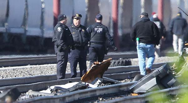 Emergency personnel stand by debris from a deadly train crash in Chester, Pa., Sunday, April 3 2016. The Amtrak train struck a piece of construction equipment just south of Philadelphia causing a derailment. (Michael Bryant/The Philadelphia Inquirer via AP)