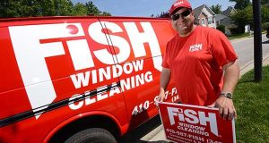 Jim Brown, Franchise owner of Fish window cleaning, standing next to one of his work vans on a job site near Annapolis. (The Daily Record/Maximilian Franz)