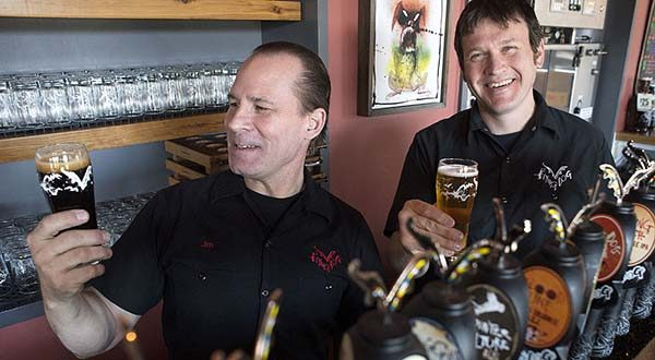 In this April 13, 2016 photo, Flying Dog Brewery CEO Jim Caruso, left, and brewmaster and COO Matt Brophy pose with two of the more than 40 beers they produce in Frederick, Md.(Dan Gross/The Frederick News-Post via AP)