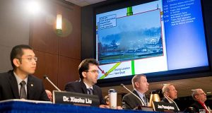 A photograph of smoke is displayed as members of a safety oversight group deliver a presentation on the probable cause of the Jan. 12, 2015 Washington Metropolitan Area Transit Authority Metrorail accident near the L'Enfant Plaza during a National Transportation Safety Board meeting in Washington, Tuesday, May 3, 2016. (AP Photo/Andrew Harnik)