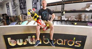 Ryan Daughtridge, Founder and CEO of  Bustin Boards custom skate board company located in City Garage, seen here holding a Maryland Themed board in the lobby of their shop.  (The Daily Record/Maximilian Franz)
