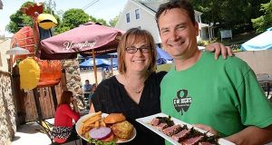 "Rachel and J. Scott Beck, owners of E.W. Beck's Pub on Main Street in Historic Sykesville, show off the restaurant's ""Colossal Crab Cake Sandwich"" and ahi tuna appetizer on the back-patio dining area. 'To witness the growth of the town has been really exciting,' says Rachel Beck. (Maximilian Franz/The Daily Record)"