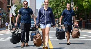 From Left,  Eli Kamerow, Marketing Manager; Kelly Desmond, Operations Manager; and Andrew Nevin, Brand Ambassador at Galley foods, walking down the center of light street in Federal Hill holding food delivery bags that their drivers use to deliver orders. (The Daily Record/Maximilian Franz)