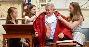 Newly sworn in Maryland Court of Appeals Judge Joseph Michael Getty, being adorned with his red robe by his three daughters in the House of Delegates Chamber in Annapolis. (The Daily Record / Maximilian Franz)