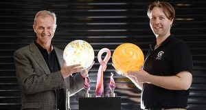 Eric A. Hanson, CEO of Zero Gravity Creations, left, and Aric Wanveer, co-founder and chairman, hold some of their company's patented glass fixtures. (Maximilian Franz/The Daily Record)