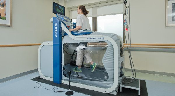 Occupational therapist Miranda Miller demonstrates an anti-gravity treadmill at FutureCare Homewood's new rehabilitation gym. (Photo courtesy of FutureCare).