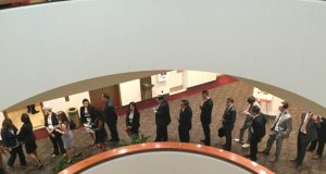 """A group of freshly sworn (or affirmed) Maryland lawyers stand in line Tuesday afternoon waiting to sign the roster of Maryland attorneys, officially called """"The Test Book."""" (Steve Lash/The Daily Record)"""