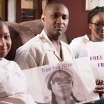 Ebrima Jawara poses last month with his daughters Sarah, left, and Aminata, while holding a picture of his wife, Fanta Darboe Jawara, who is being held in Gambia's notorious Mile 2 Central Prison, as they anxiously await her return to their Frederick. Jawara says his wife, a naturalized U.S. citizen, has been wrongfully sentenced to three years imprisonment in Gambia following her arrest during an anti-government protest where her husband says she was a bystander during a visit to her homeland.  (Bill Green/The Frederick News-Post via AP)