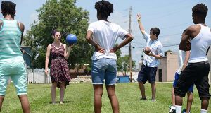 Amanda Sabino and Aaron Bruzzese, program directors for the Substance Use and Delinquency Prevention programs, rally some children at the Dundalk Youth Service Center to play some games out in the field behind their office. Programs like these are suffering cutbacks because the governor is withholding funding. (The Daily Record/Maximilian Franz)