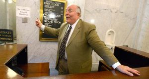 """ruce Bereano pointing to a sign that reads """" No Lobbyists Beyond This Point"""" in the State house lobby. (The Daily Record / Maximilian Franz)"""