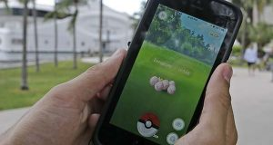 """Exeggcute, a Pokemon, is found by a  Pokemon Go player, Tuesday, July 12, 2016, at Bayfront Park in downtown Miami. The """"Pokemon Go"""" craze has sent legions of players hiking around cities and battling with """"pocket monsters"""" on their smartphones. It marks a turning point for augmented reality, or technology that superimposes a digital facade on the real world. (AP Photo/Alan Diaz)"""
