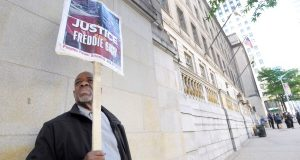 Arthur B. Johnson Jr., of Baltimore, demonstrates alone in June outside Baltimore City Circuit Court on the first day of the trial of Officer Caesar Goodson, one of six Baltimore city police officers charged in connection to the death of Freddie Gray. Despite back-to-back acquittals for officers charged in Gray's death, the physical protest movement that helped topple the careers of both the police commissioner and the mayor has dissipated, leaving activists exploring other avenues for change. (Steve Ruark/AP file photo)