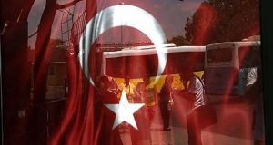 People reflected on glass with Turkish a flag at a bus station in Istanbul, Monday, July 25, 2016. (AP Photo/Petros Karadjias)