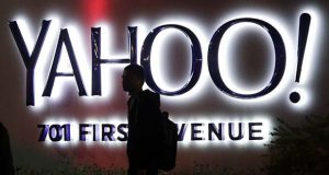 FILE - In this Nov. 5, 2014, file photo, a person walks in front of a Yahoo sign at the company's headquarters in Sunnyvale, Calif. Verizon bought Yahoo in a sale announced Monday, July 25, 2016. (AP Photo/Marcio Jose Sanchez, File)