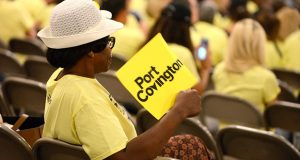East Baltimore resident Christine Thornton, owner of Chandler Enterprises, which provides clerical support services fans herself with a Port Covington sign during the hearing at the War Memorial Building, which was attended by over 200 people. (The Daily Record/Maximilian Franz)