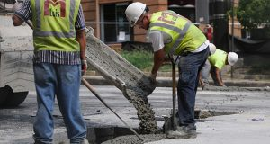 08.17.12- BALTIMORE, MD- Workers from M.Luis Construction are seen here filling in holes with concrete as part of the  water main break repairs on Light Street. (Maximilian Franz/The Daily Record).