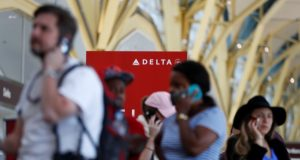Travelers talk on their cell phones as they stand in line at the Delta ticketing counter at Washington's Ronald Reagan Washington National Airport, Monday, Aug. 8, 2016. (AP Photo/Carolyn Kaster)