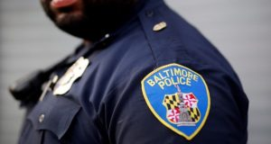 In this March 31, 2016, file photo, Baltimore Police Department Officer Jordan Distance stands on a street corner during a foot patrol in Baltimore. Baltimore police officers routinely discriminate against blacks, repeatedly use excessive force and are not adequately held accountable for misconduct, according to a harshly critical Justice Department report being presented Wednesday, Aug. 10, 2016. (AP Photo/Patrick Semansky, File)