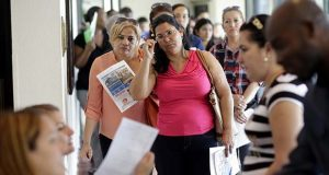 In this Tuesday, July 19, 2016, photo, Reina Borges, left, stands in line to apply for a job with Aldi at a job fair in Miami Lakes, Fla. (AP Photo/Lynne Sladky)