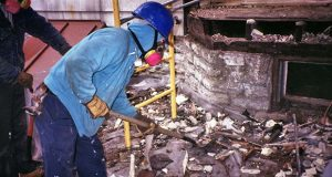 This 1993 photograph shows two masked workers removing debris from a bay window that had been dismantled by hand, demonstrating exterior renovation methods typically used on residences where lead-based paint was present. (Centers for Disease Control and Prevention photo)