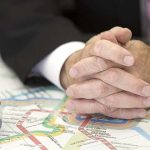Metro General Manager Paul Wiedefeld is seen in his office with a map of the subway system on the conference table beneath his hands, in Washington, Thursday, July 7, 2016. (AP Photo/Cliff Owen)