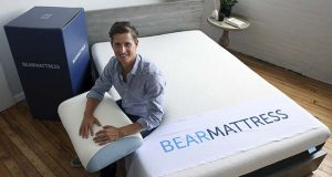 In this Tuesday, Aug. 16, 2016, photo, Scott Paladini, CEO of Bear Mattress, sits with a sample Bear Mattress, a newly-designed pillow and a shipping box in the company showroom in Hoboken, N.J. Bear Mattress has seen sales from mobile devices increase since it was launched in 2015. About half now come from phones and tablets and Paladini expects that to grow because 85 percent of company's online visitors are using mobile devices. (AP Photo/Mel Evans)