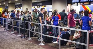 People wait in the Southwest Airlines check-in line at Sky Harbor International Airport.