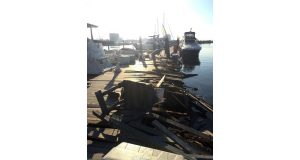 In this Sunday, Aug. 28, 2016 photo released by the U.S. Coast Guard, people walk near damage to a dock after the Spirit of Baltimore crashed in Baltimore. Spirit Cruises said the captain of the cruise ship that crashed has been suspended from duty. (Chief Warrant Officer Tom Davan/U.S. Coast Guard via AP)