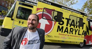 Mike Binko stands next to the Startup Maryland Bus during its tour stop at University of Baltimore. (Maximilian Franz / The Daily Record)