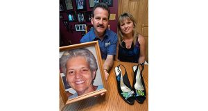 This Aug. 11, 2016 photo shows Jimmy Trout and his wife Cynthia with a photograph of Jimmy's mother, Ann Sue Metz, who was murdered in Frederick in 2009 by her husband. Marshall Metz died in prison but Trout received an automated call that Metz 'had been released from custody.' Prison officials apologized for the miscommunication and pledged to revamp the system. (Dan Gross/The Frederick News-Post via AP)