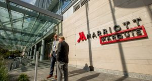 In this Wednesday, Oct. 14, 2015, file photo, two men stand outside the newly-built Marriott Marquis hotel in Washington. Marriott International closed early Friday, Sept. 23, 2016, on its acquisition of Starwood Hotels & Resorts Worldwide, bringing together its Marriott, Courtyard and Ritz-Carlton brands with Starwood's Sheraton, Westin, W and St. Regis properties. (AP Photo/Andrew Harnik, File)