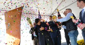 Mayor Stephanie Rawlings Blake is showered with confetti after christening the Liberty Harbor East project with a bottle of champagne at the groundbreaking on Friday. (The Daily Record / Maximilian Franz)